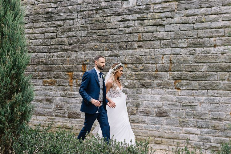 Bride in Fitted Mikaella Wedding Dress with Flower Crown and Groom in Bespoke Navy Check Suit by Territo Walking in the Grounds of Elmore Court