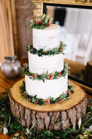 Rustic Wedding Cake Decorated with Foliage and Figs on a Tree Stump Cake Stand