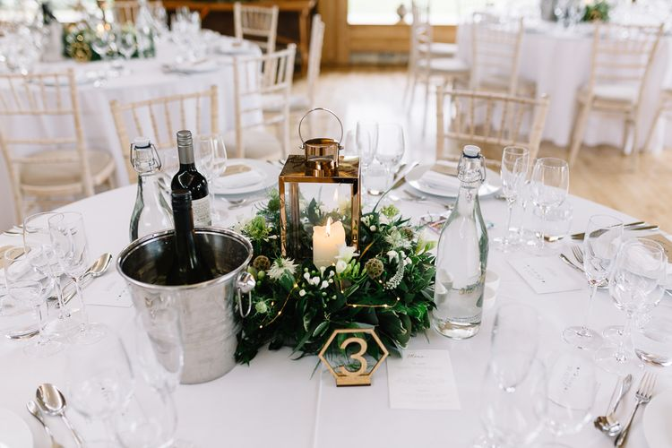 Table Centrepiece Lantern Surrounded by White and Green Wedding Flowers