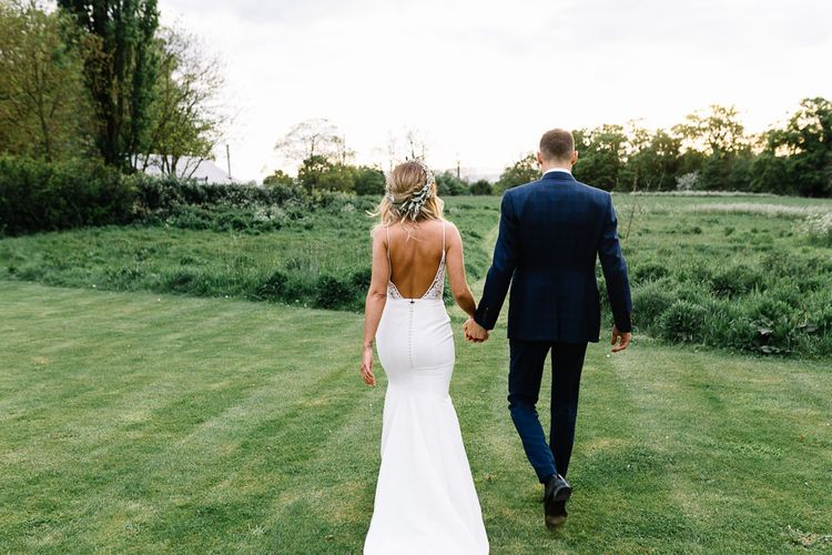 Bride in Fitted Mikaella Wedding Dress with Low Back and Flower Crown and Groom in Bespoke Navy Check Suit Holding Hands
