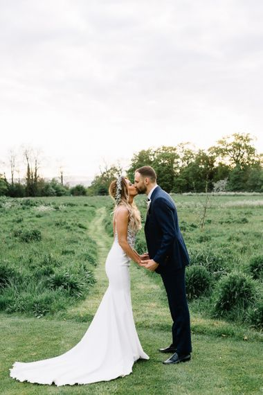 Bride in Fitted Mikaella Wedding Dress  and Flower Crown and Groom in Bespoke Navy Check Suit Kissing