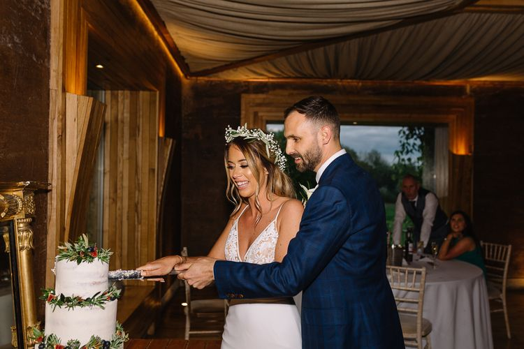 Bride in Fitted Mikaella Wedding Dress  and Flower Crown and Groom in Bespoke Navy Check Suit Cutting the Wedding Cake