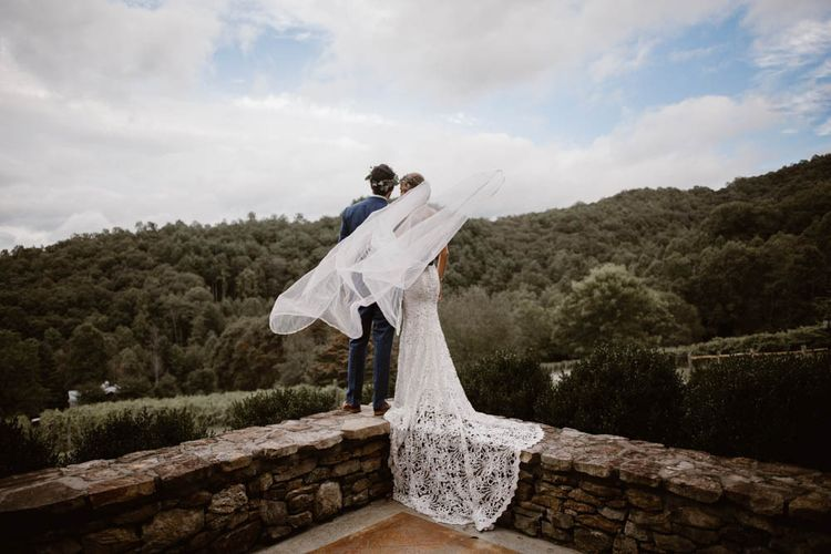 Bride and Groom Look Out Over Landscape