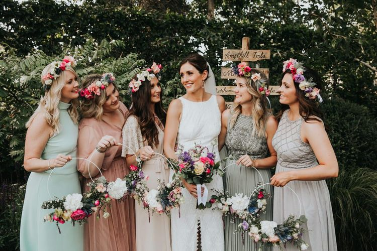 Different bridesmaid dresses with hoop bouquets and flower crowns