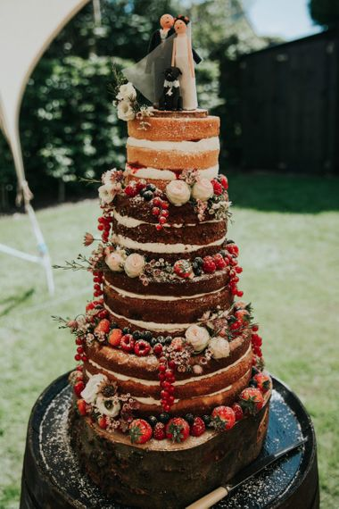 Naked wedding cake with berries and cake topper