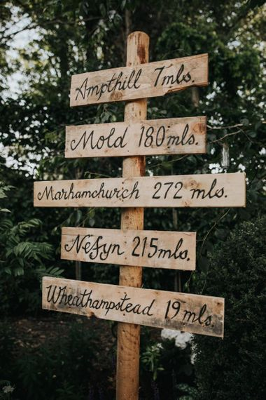 Wooden wedding sign at celebration with different bridesmaid dresses