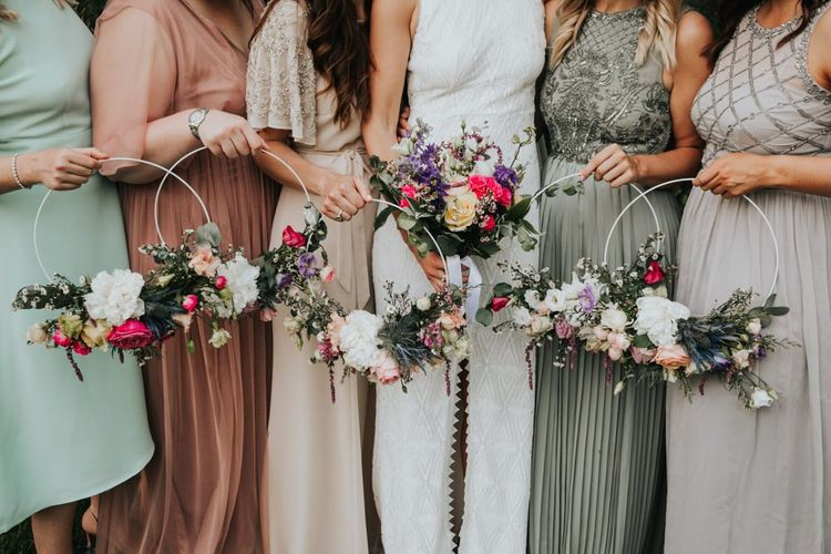 Bridal party in different bridesmaid dresses with hoop bouquets