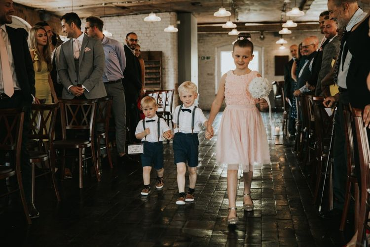 Bridesmaid and page boys walk down the