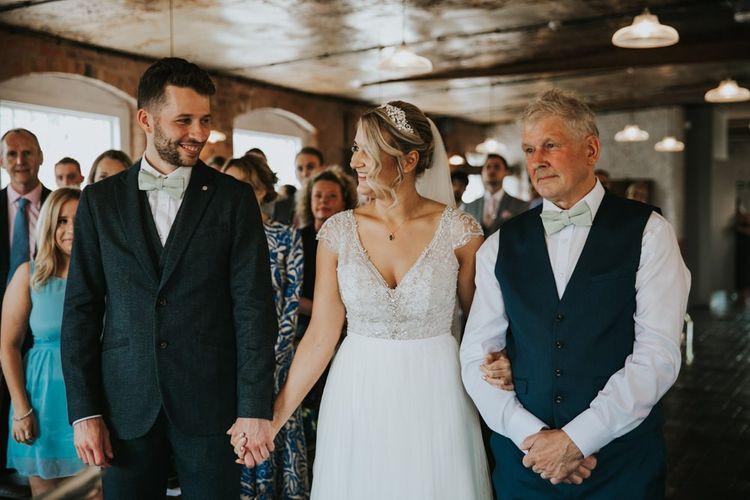 Bride in Stella York wedding dress greets groom