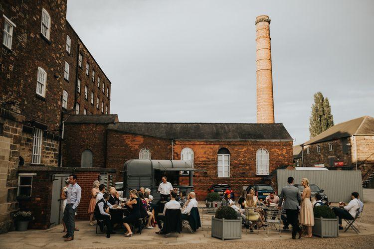Guests enjoy a drink outside mill wedding venue