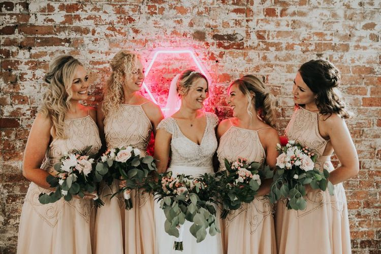 Blush bridesmaid dresses with bride in Stella York wedding dress