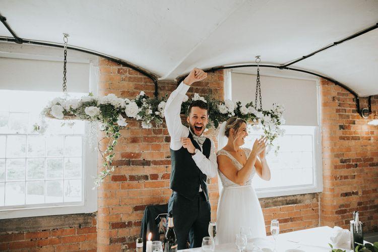 Bride in Stella York wedding dress celebrating with groom