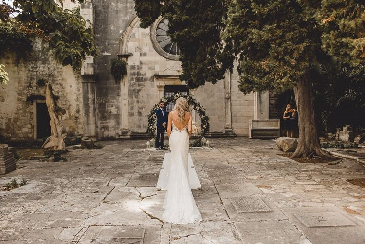 Bride walks up to meet groom in Essense of Australia dress