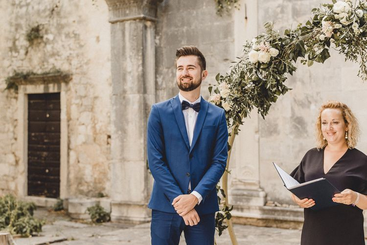 Groom waits for bride in front of floral moon gate