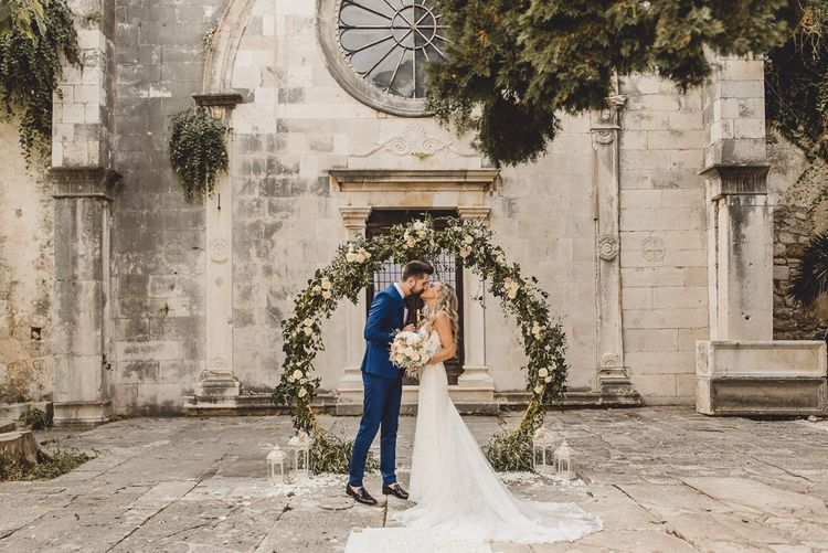 Bride and groom kiss in front of floral moon gate