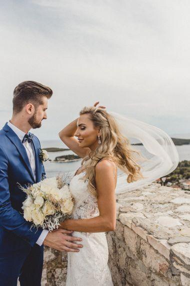 Bride wears hair in Hollywood waves with veil
