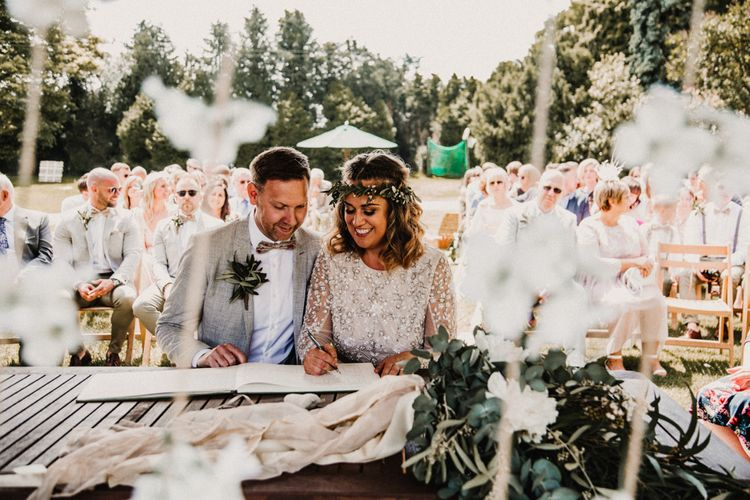 Wedding Ceremony | Signing the Register | Boho Bride in Sequin & Tulle Needle & Thread Gown | Groom in Chinos, Braces & Bow Tie | Rustic, Boho, Outdoor Summer Garden Wedding at Herons Farm, Berkshire | Carla Blain Photography