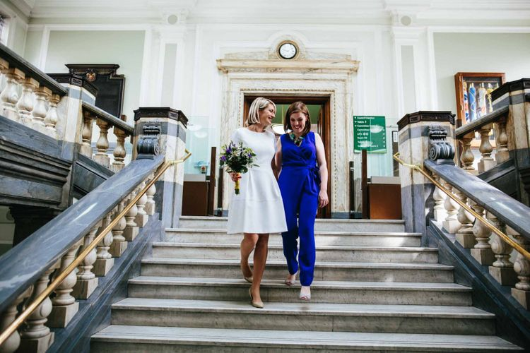 Lesbian wedding with brides in short wedding dress and blue jumpsuit