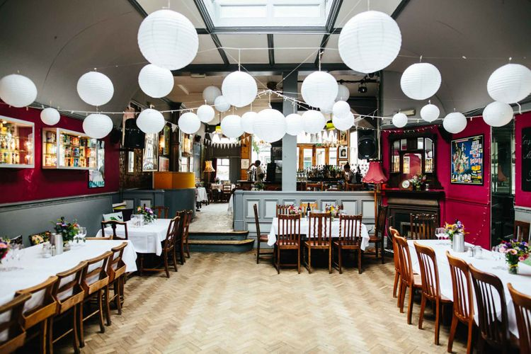Same sex pub reception with paper lanterns and fairy lights strung from the ceiling