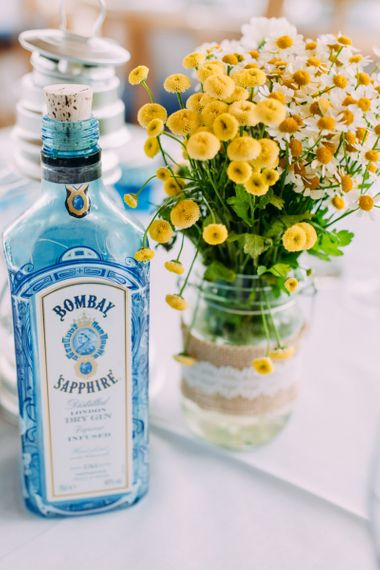 Blue Gin bottle and yellow flowers in jars