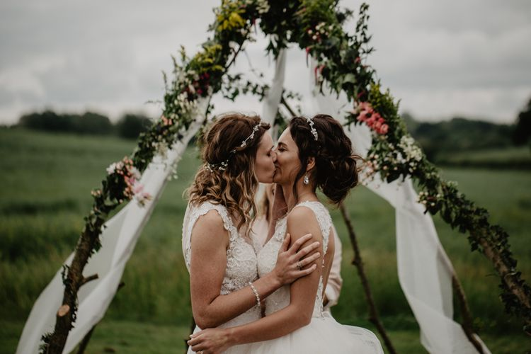 Two brides kissing in front of a naked tipi altar at outdoor wedding