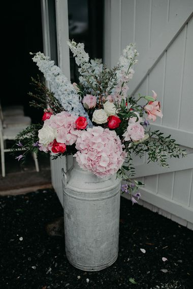 Milk churn with pink hydrangeas and blue stocks
