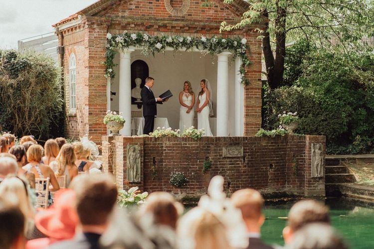Lesbian wedding at Micklefield Hall with outdoor ceremony by the pond