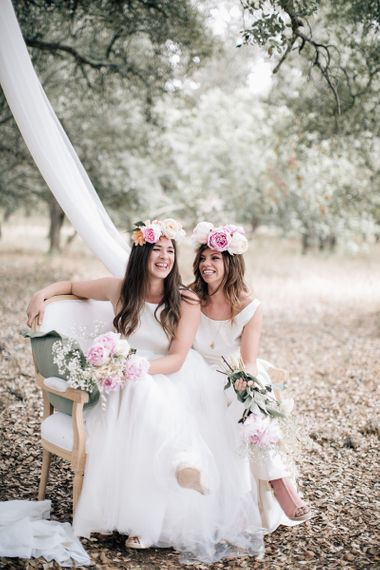 Same sex wedding ceremony with brides in matching pink peony flower crowns