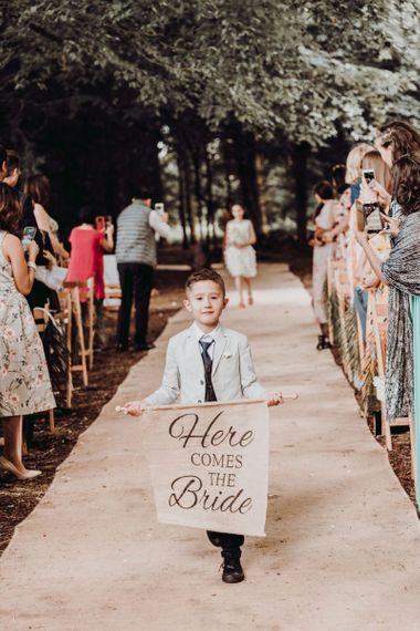 Page boy walking down the aisle with here comes the bride sign at Charisworth Farm wedding