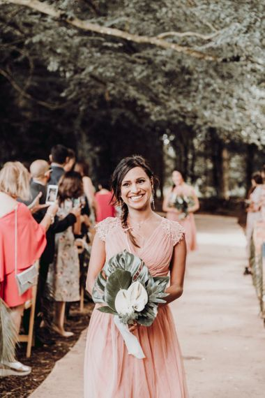 Beautiful bridesmaid in pink dress with side plait and tropical bouquet