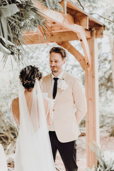 Groom in beige blazer and bride with wedding veil