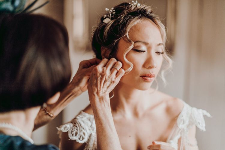 Bride putting on her wedding day earrings