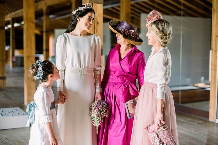 Bridal party portrait with guests in pink dresses and bride holding a astilbe wedding bouquet