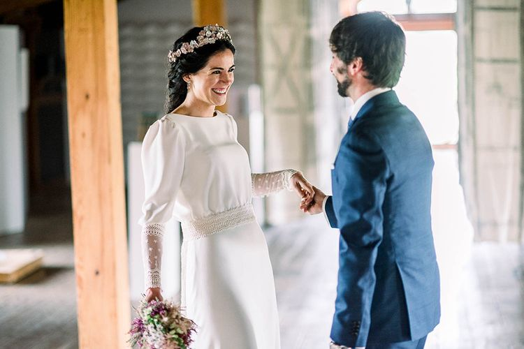Bride and groom first look with bride in Victoria Imaz wedding dress holding a astilbe wedding bouquet