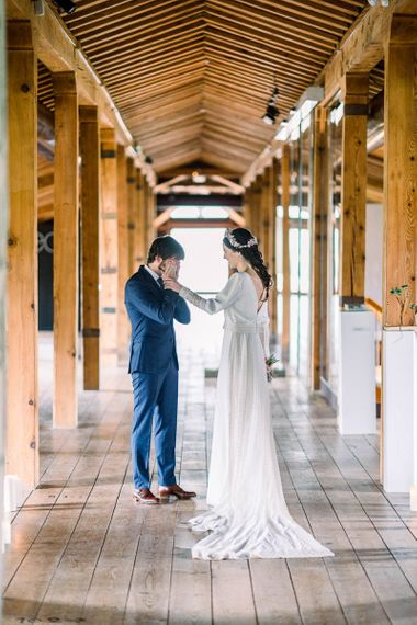 Emotional groom in navy suit at first look