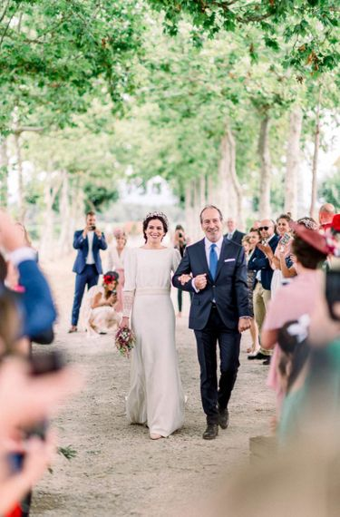 Wedding ceremony bridal entrance with bride walking down the aisle in Victoria Imaz dress