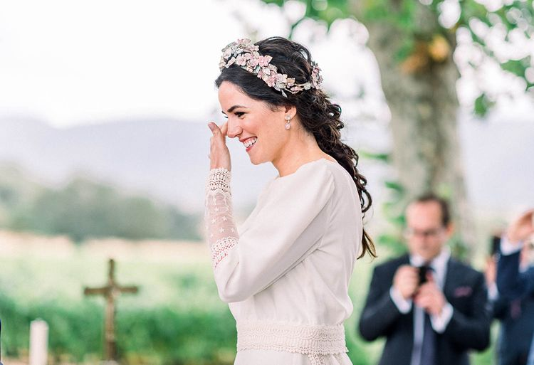Emotional bride wiping away tears at the wedding ceremony in a pink flower headdress