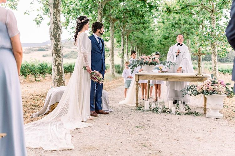 bride and groom standing at the altar of the wedding ceremony with the bride holding an astilbe wedding bouquet