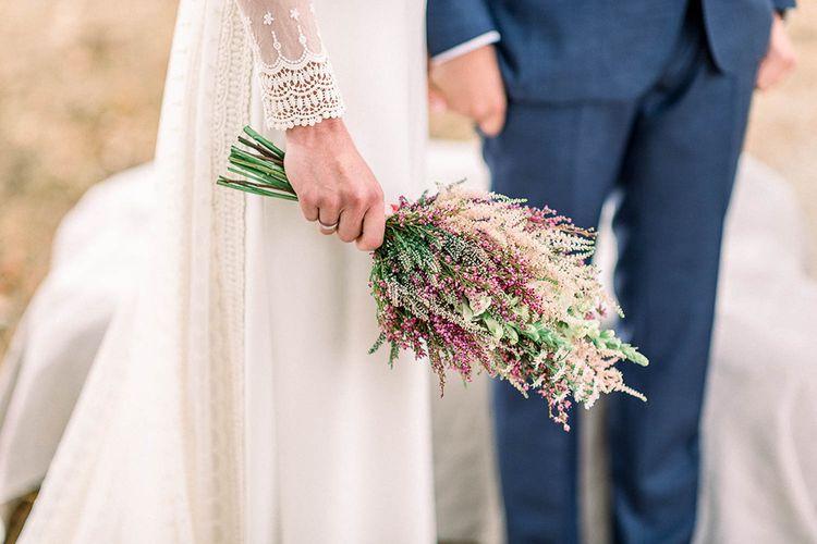 Bride in lace cuff sleeve wedding dress holding an astilbe wedding bouquet