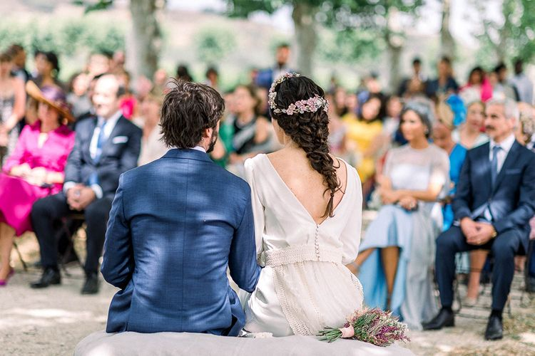 Bride in low V back wedding dress with  fishtail braid,  flower headdress and astilbe wedding bouquet