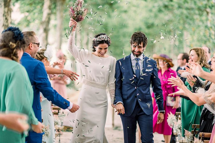 Olive leaf confetti exit with bride holding her astilbe wedding bouquet in the air
