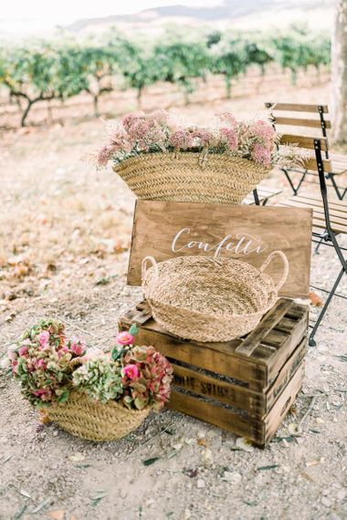 Rustic wedding decor with wooden sign, crates and wicker baskets filled with flowers