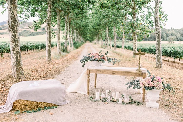 Romantic altar wedding decor with hay bale, and pink floral arrangements