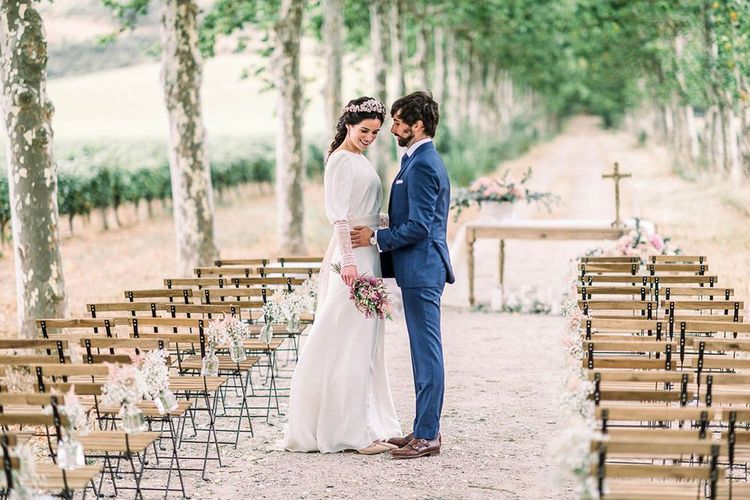 Bride and groom standing in the aisle holding an astilbe wedding bouquet