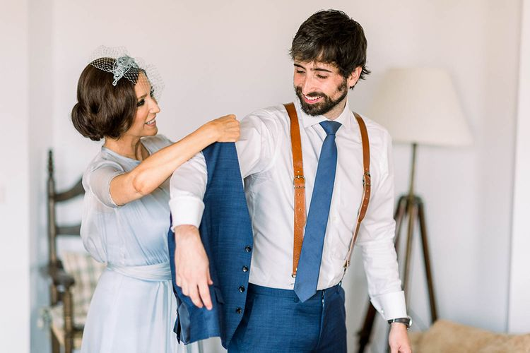 Mother of the bride helping the groom into his navy waistcoat