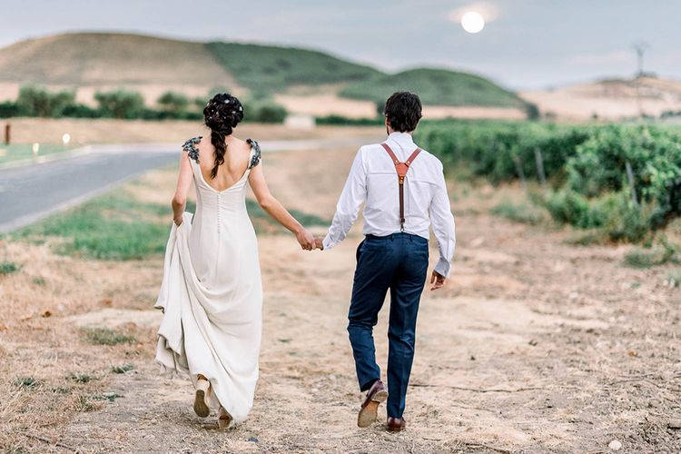 Bride and groom holding hands walking into the sunset