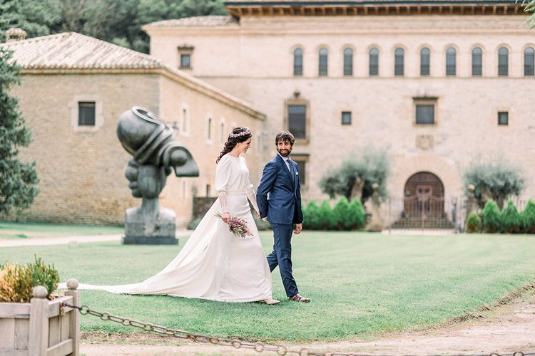 Bride and groom at Otazu Wineries wedding venue with bride holding an astilbe wedding bouquet