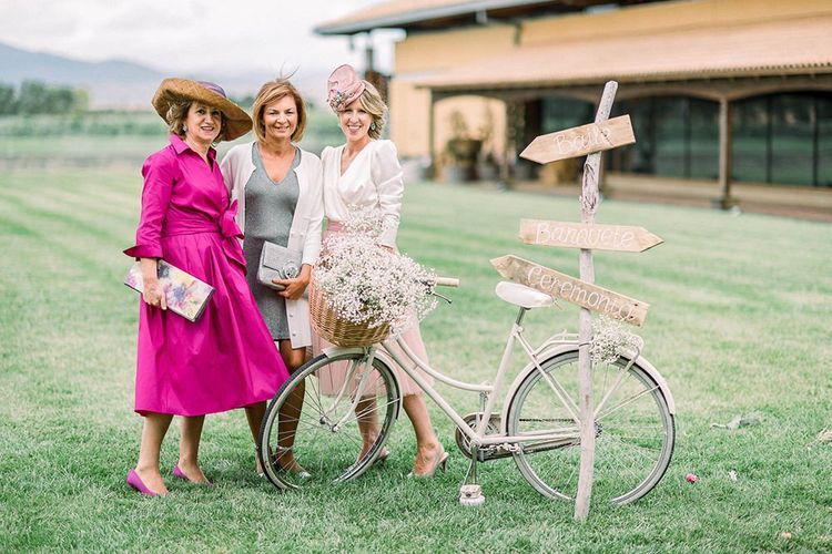 Wedding guests posing by a vintage bicycle filled with gypsophila