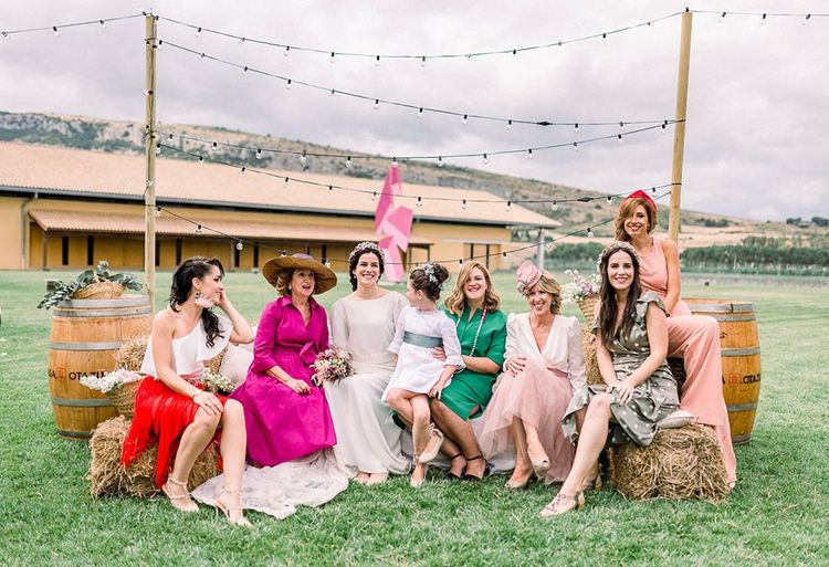 Female wedding guests sitting on a hay bale seating area