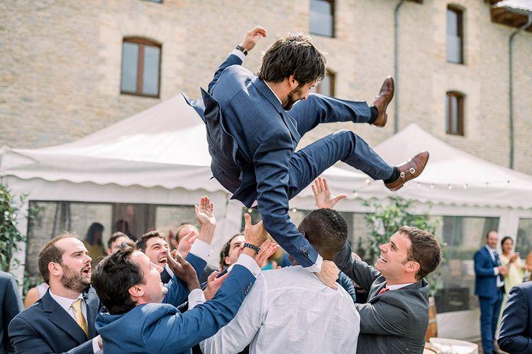 Groomsmen throwing the groom in the air